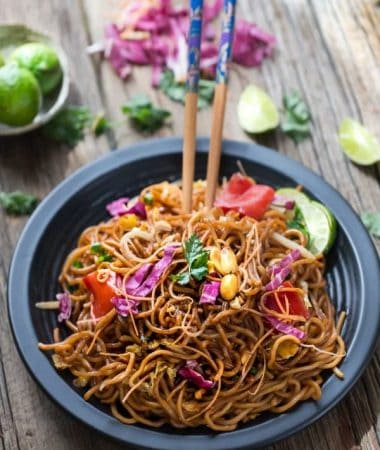 Rainbow Asian Skillet Peanut Noodles in a black bowl with chopsticks