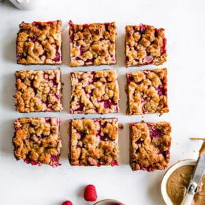 Top view of 9 raspberry pie bars on on a white background