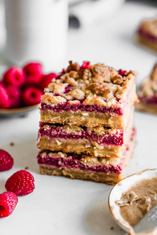 Front view of three raspberry bars stacked on white surface with fresh raspberries.
