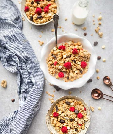 Raspberry Double Chocolate Granola makes the perfect gluten free breakfast or after school / pre or post workout snack. Loaded with crunchy clusters, shredded coconut, white and dark chocolate chips along with freeze-dried and fresh raspberries. Best of all, this recipe is gluten free and refined sugar free and works great for Sunday meal prep.