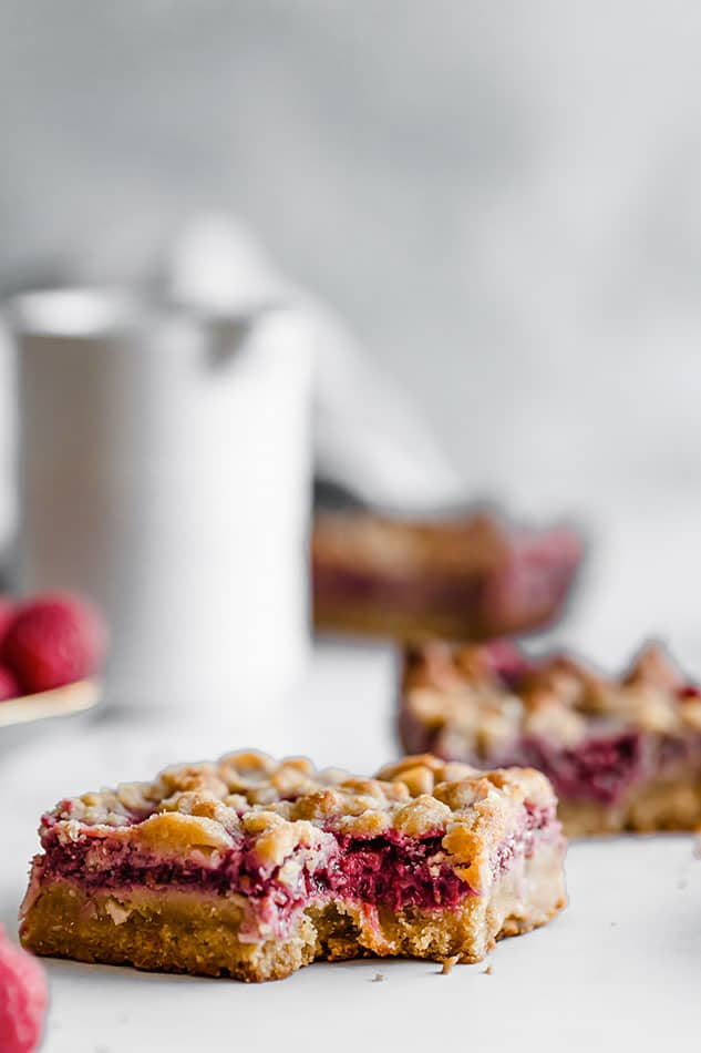 Front view of raspberry crumb bar on white surface.