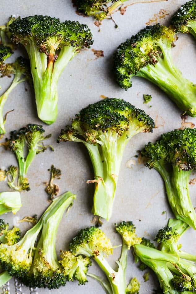 Overhead view of roasted broccoli on baking sheet.
