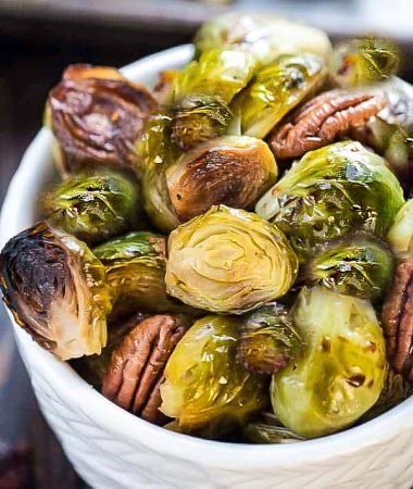 Roasted Brussels sprouts in a white bowl with pecans