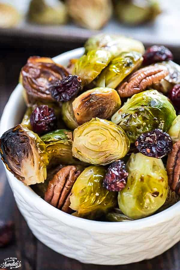 Roasted Brussels sprouts in a white bowl with pecans and dried cranberries