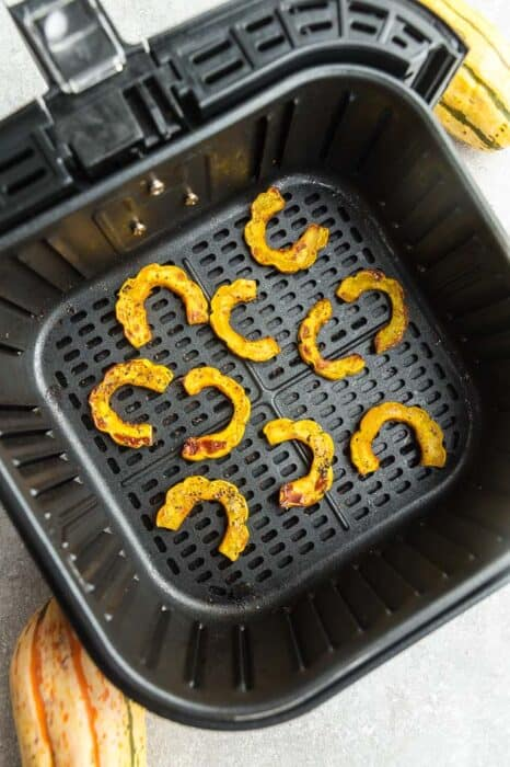 Top view of cooked delicata squash cut into half rings in an air fryer basked