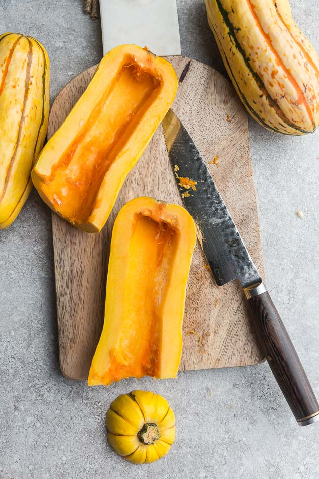 Top view of raw delicata squash cut into halves lengthwise on a wooden cutting board with a knife
