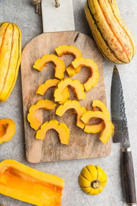 Top view of raw delicata squash cut into half rings lengthwise on a wooden cutting board with a knife