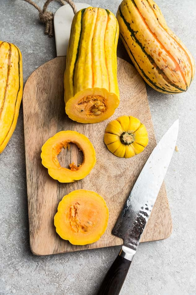Top view of raw delicata squash cut into rings on a wooden cutting board with a knife