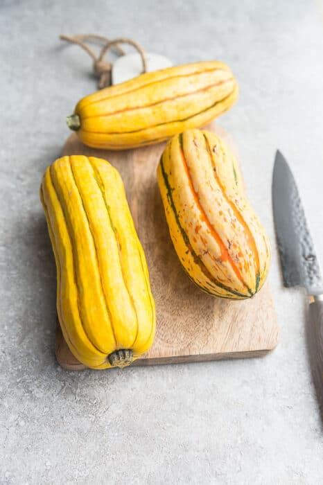 Top view of 3 whole delicata squash on a wooden cutting board with a knife