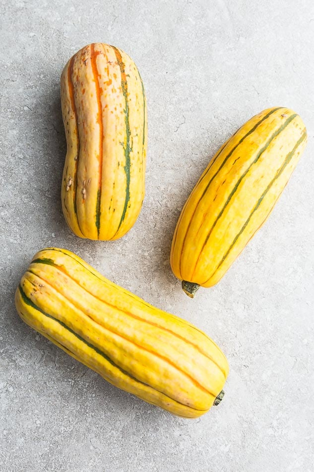 Top view of 3 whole delicata squash on a grey background