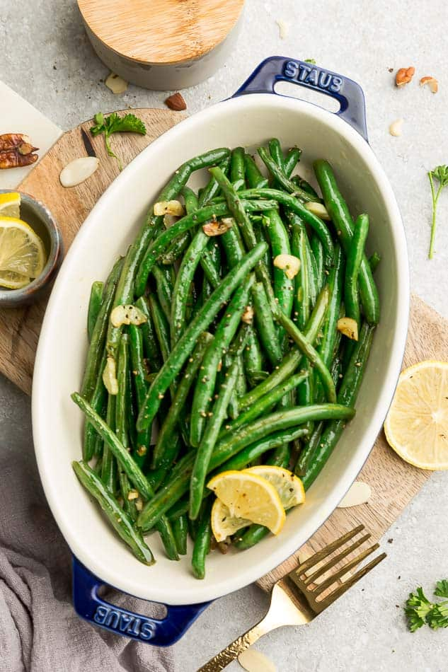 Top view of roasted green beans with garlic in a oval blue casserole dish on a wooden cutting board