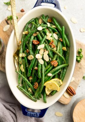 Top view of roasted green beans with slivered almonds and pecans in a oval blue casserole dish on a wooden cutting board