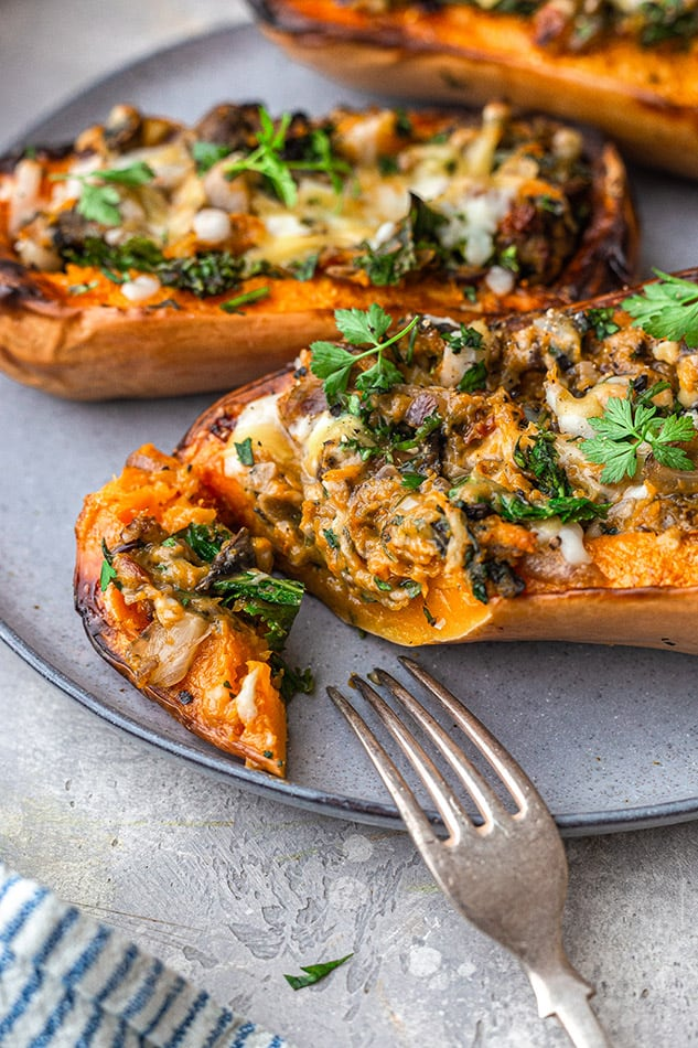 Close-up of three stuffed butternut squash halves on a plate with a bite cut out of one