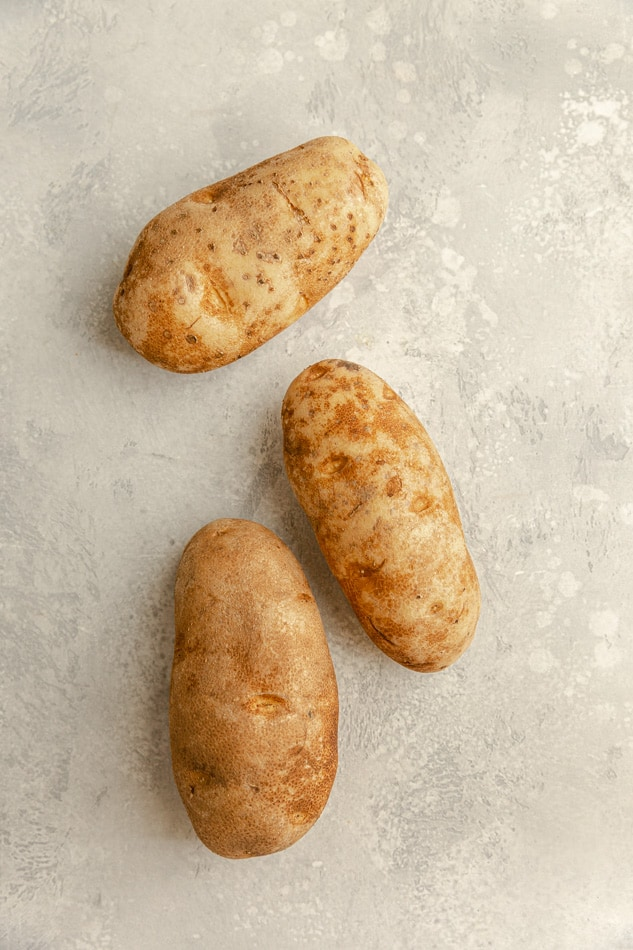 3 uncooked russet potatoes on a gray background