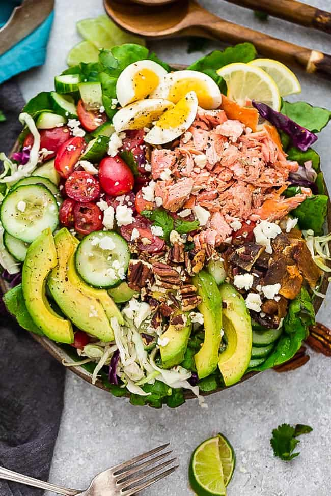 Salmon Cobb Salad is a lightened up twist on the classic Cobb Salad. It's made with grilled or broiled salmon, cucumber, eggs, tomatoes, avocado, crispy bacon and a creamy and tangy vinaigrette. Low carb, keto , gluten free with Whole 30 & paleo friendly options.