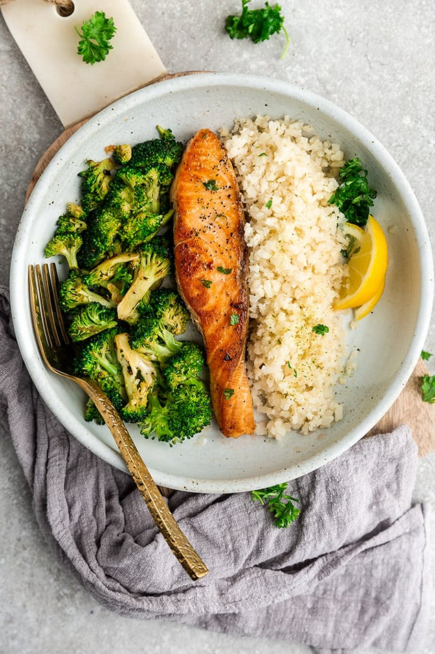 Top view image of keto cauliflower rice in a white bowl served with salmon and broccoli