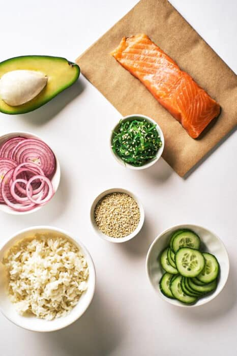 Top view of raw salmon poke bowl ingredients