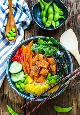 Top view of salmon poke bowl with chopsticks on a wooden background
