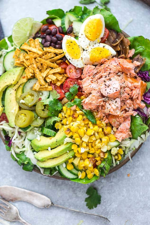 Overhead view of Salmon Taco Salad with corn, avocado, eggs, and tortilla strips