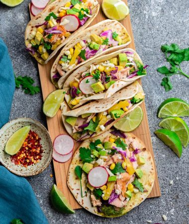 Easy Salmon Tacos - packed with flavor and come together in 30 minutes - perfect for your next Taco Tuesday! Topped with lettuce, red cabbage, corn, pineapple and avocado cream