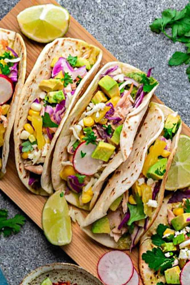 Easy Salmon Tacos - packed with flavor and come together in 30 minutes - perfect for your next Taco Tuesday! Topped with lettuce, red cabbage, corn, pineapple and avocado cream.
