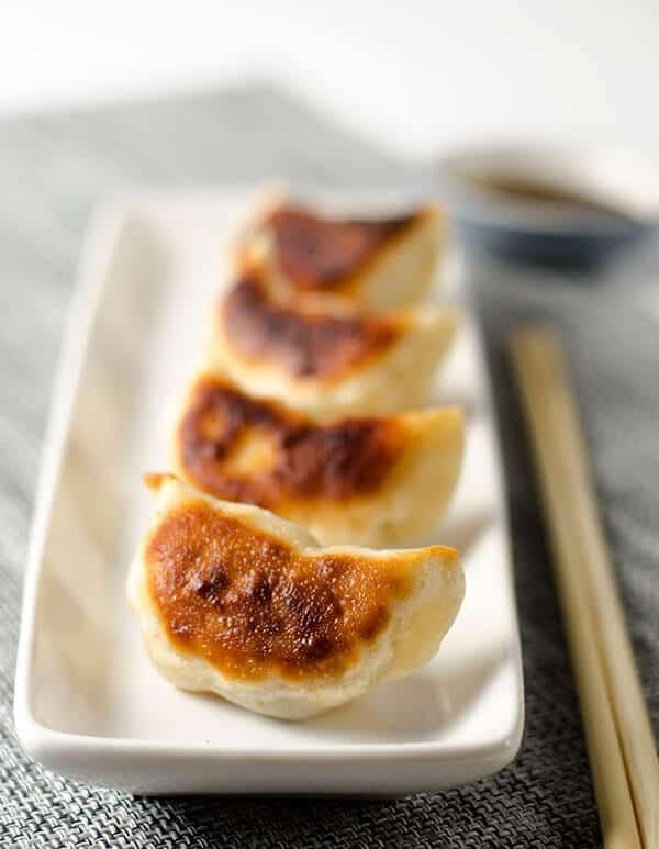 Four browned dumplings on a rectangular plate
