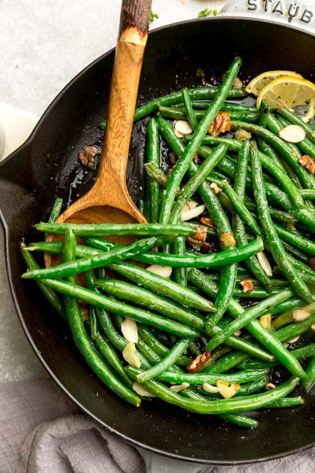 Fresh green beans sauteed in black pan with wooden spoon.