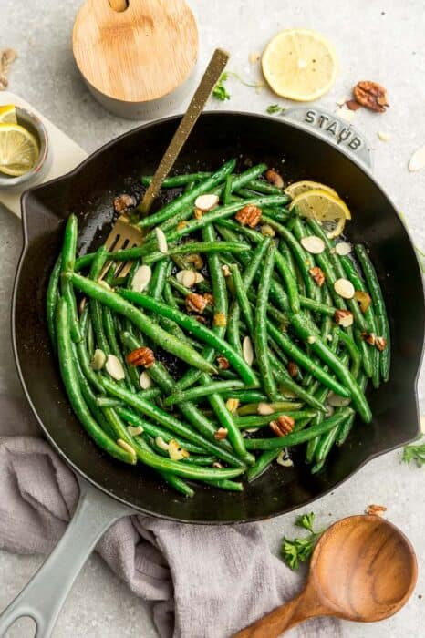 Top view of sauteed green beans in a grey cast iron skillet with a gold fork on a grey background