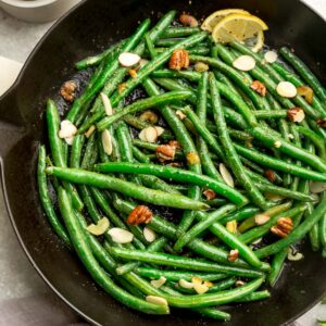Close-up top view of sauteed green beans in a grey cast iron skillet on a grey background