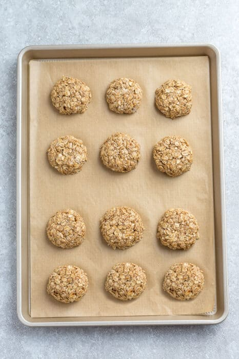 Top view of 12 tahini cookies on a baking sheet on a grey background