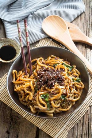 Shanghai Fried Noodles in a small bowl with dark brown chopsticks.