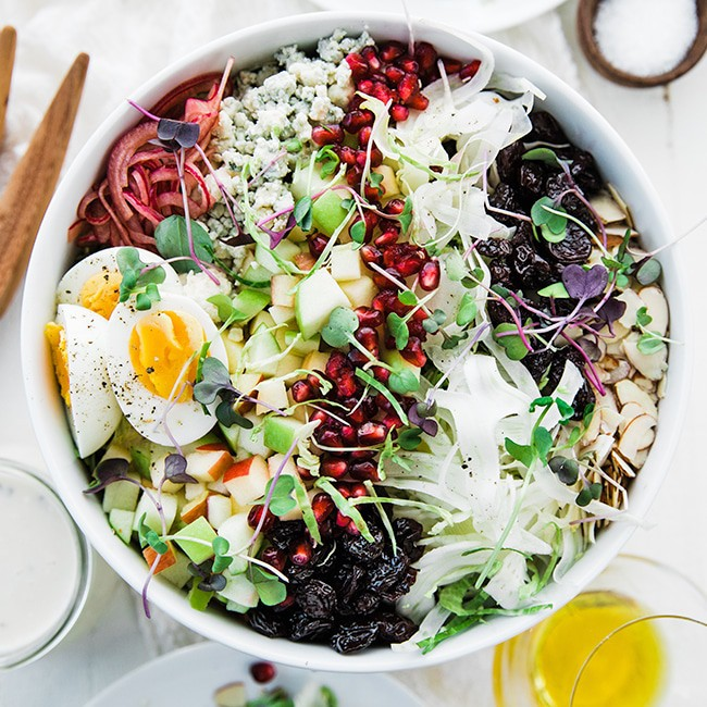 Overhead view of Shaved Brussels Sprouds Salad with egg, dried fruit, and sprouts