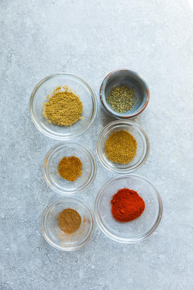 Top view of six clear bowls of shawarma seasoning mix on a grey background