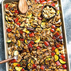 Top view of Sheet Pan Kung Pao Chicken with vegetables and a cup of cashews
