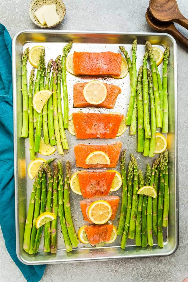 Top view of raw salmon filets on a sheet pan with asparagus and lemon