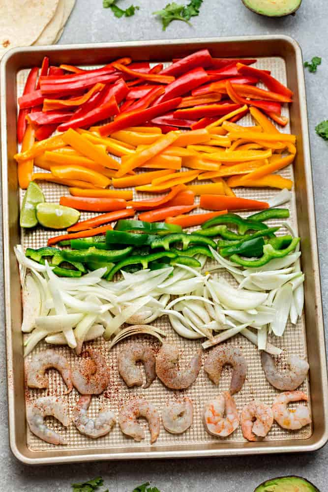 uncooked bell peppers, onions, and shrimp on a sheet pan for a sheet pan fajitas dinner