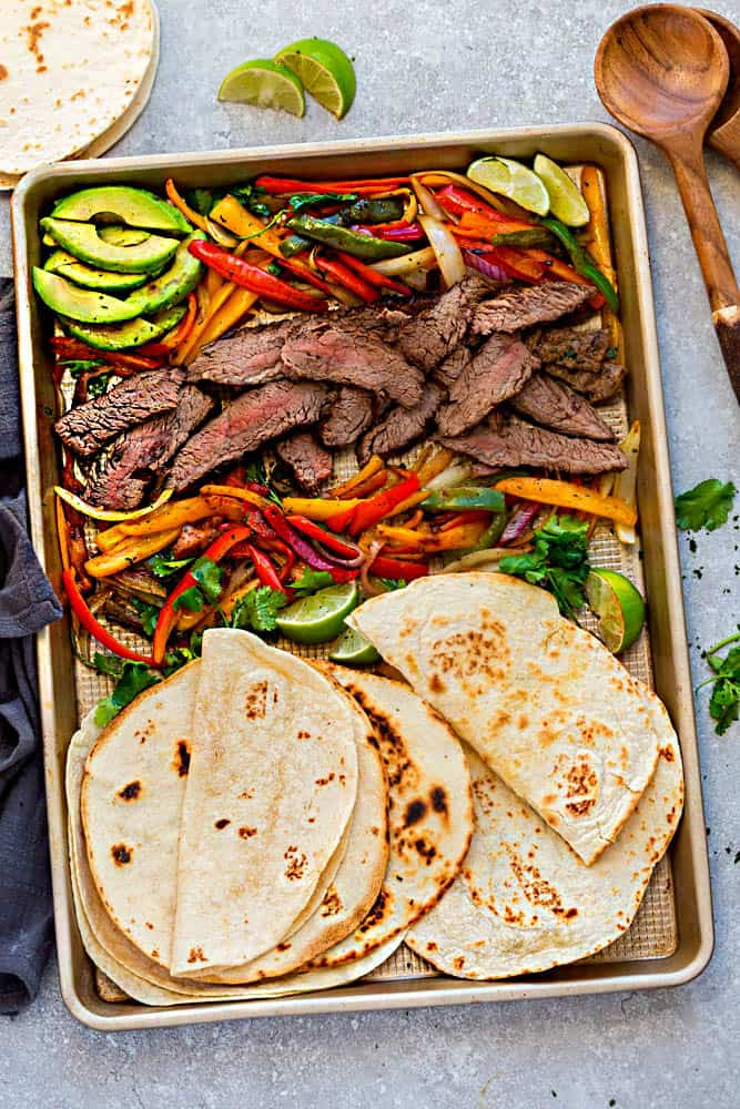 Steak fajitas made on a sheet pan with vegetables and tortillas.
