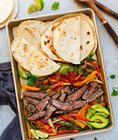 Top view of Sheet Pan Steak Fajitas on a baking sheet with avocado, lime and Whole30 tortillas