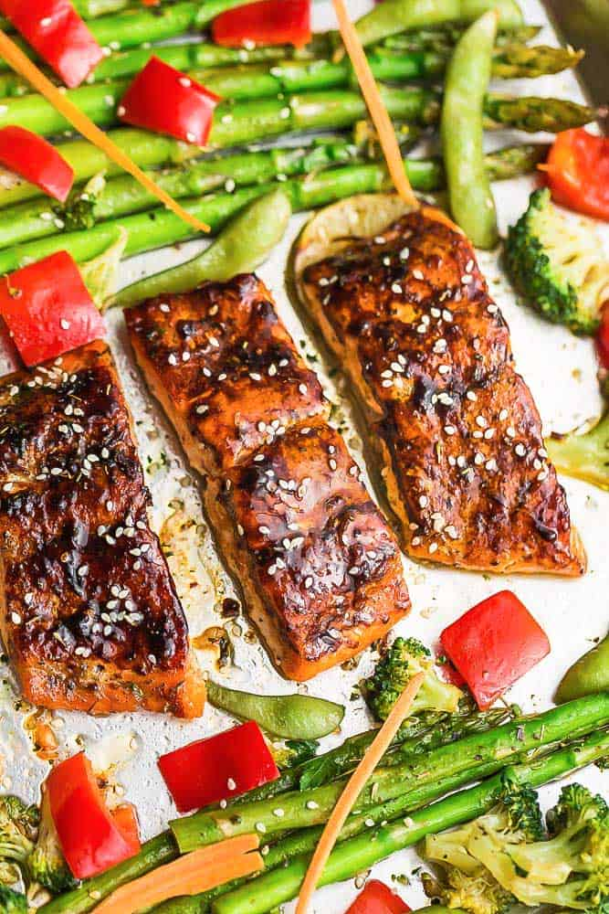 Asian Teriyaki Baked Salmon surrounded by roasted asparagus, broccoli, and red bell peppers