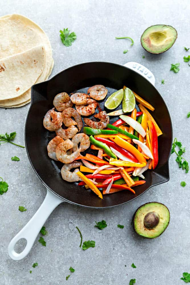 Uncooked shrimp and bell peppers in a white skillet