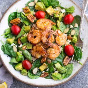 Top view of shrimp salad on a white plate on a grey background with a fork
