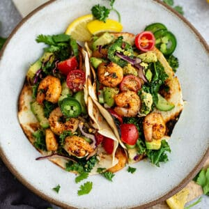 Top view of 2 paleo shrimp tacos on a white plate on a grey background