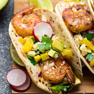 Healthy Shrimp Tacos - made with a delicious spicy seasoning and come together in 30 minutes – perfect for your next Taco Tuesday! Best of all, instructions to make this on the grill or stove and packed with avocado, lettuce, red cabbage, pineapple and avocado cream.