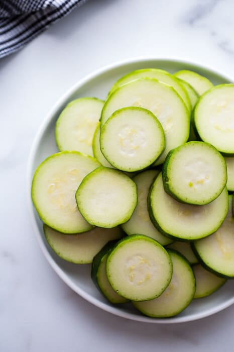 Top view of raw zucchini rounds in a white bowl