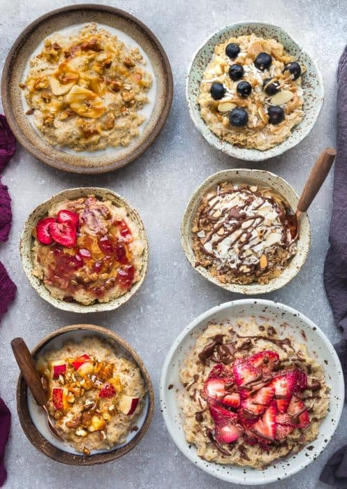 Six Bowls of Oatmeal on a Gray Counter with Different Fruits, Nuts and Nut Butters on Top