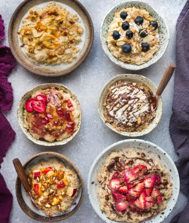 Top view of six basic oatmeal bowls with different toppings on a grey background with a spoon and napkins