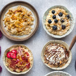 Top view of six oatmeal bowls with different toppings on a grey background with a spoon and napkins