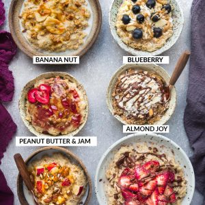 Top view of six healthy oatmeal bowls with different toppings on a grey background with a spoon and napkins and