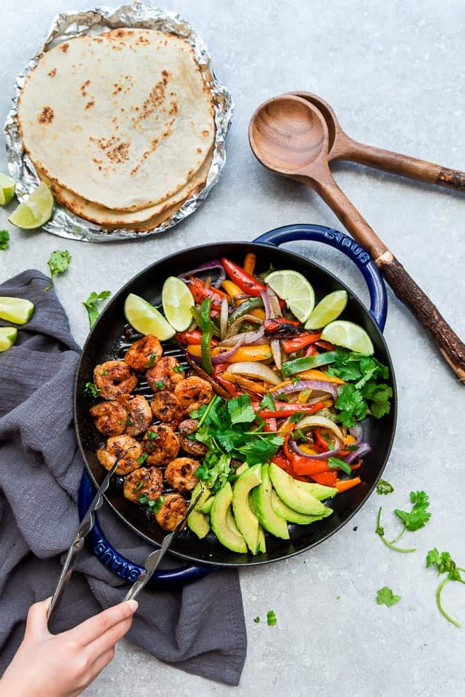 Skillet Shrimp Fajitas with avocado and bell peppers in a blue cast iron skillet with tongs