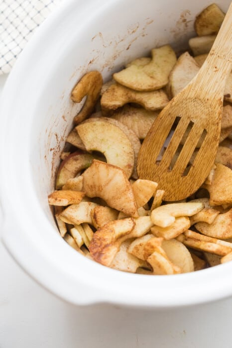 Sliced and seasoned apples in a slow cooker